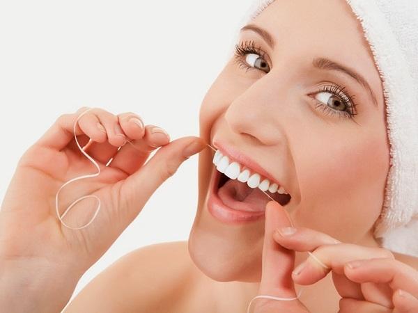 Sử dụng chỉ nha khoa để vệ sinh răng miệng.